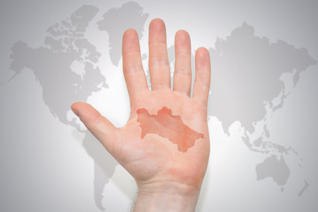 hand with map of turkmenistan on the gray world map background. concept