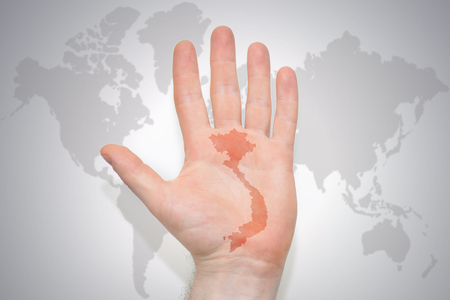 hand with map of vietnam on the gray world map background. concept