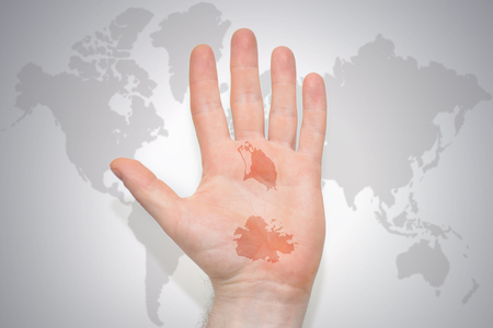 hand with map of antigua and barbuda on the gray world map background. concept
