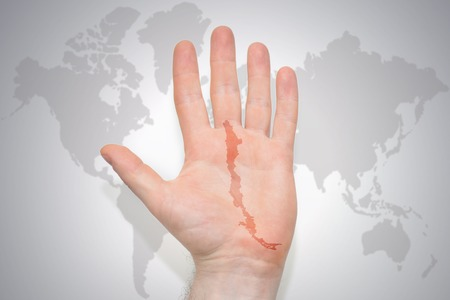 hand with map of chile on the gray world map background. concept Stock Photo