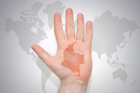 hand with map of colombia on the gray world map background. concept