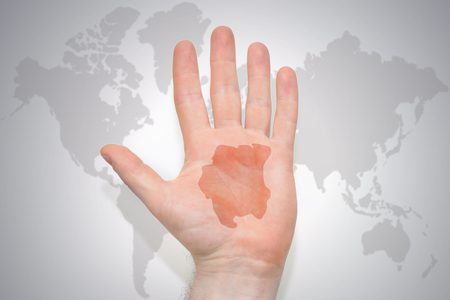 hand with map of suriname on the gray world map background. concept Stock Photo