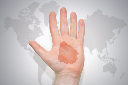 hand with map of uruguay on the gray world map background. concept Stock Photo