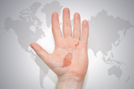 hand with map of grenada on the gray world map background. concept Stock Photo