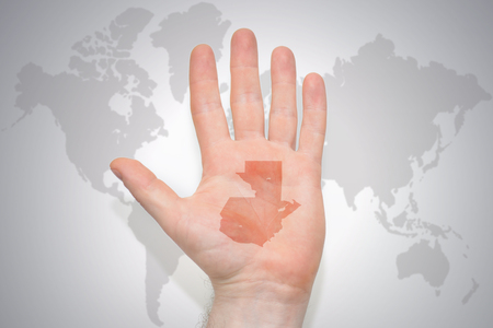 hand with map of guatemala on the gray world map background. concept