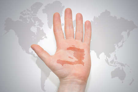 hand with map of haiti on the gray world map background. concept Stock Photo