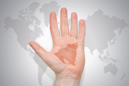 hand with map of nicaragua on the gray world map background. concept