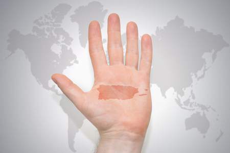 hand with map of puerto rico on the gray world map background. concept