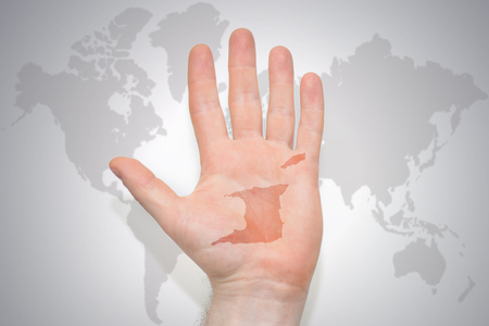 hand with map of trinidad and tobago on the gray world map background. concept