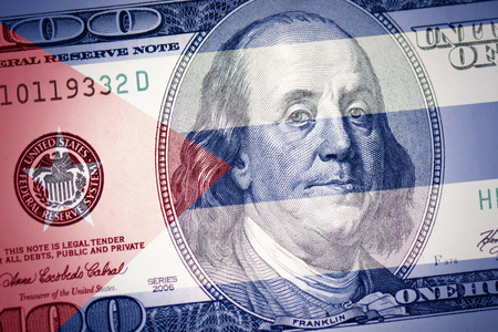 kolorowa flaga Kuby na tle pieniędzy w dolarach amerykańskich