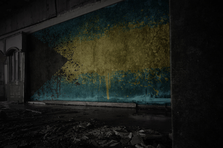 painted flag of bahamas on the dirty old wall in an abandoned ruined house. concept