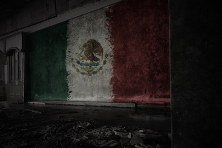 painted flag of mexico on the dirty old wall in an abandoned ruined house. concept Stock Photo