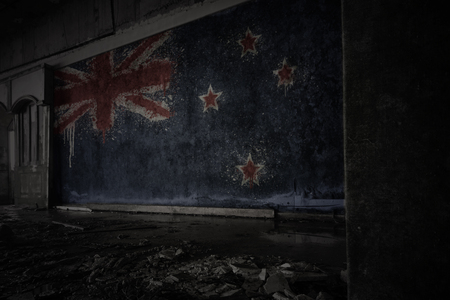 painted flag of new zealand on the dirty old wall in an abandoned ruined house. concept Stok Fotoğraf