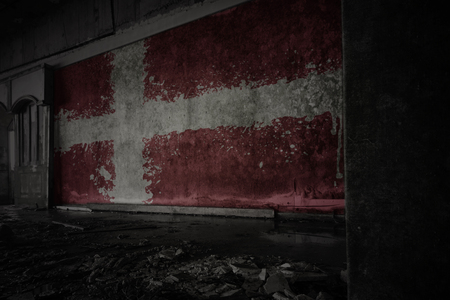 painted flag of denmark on the dirty old wall in an abandoned ruined house. concept