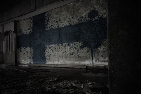 painted flag of finland on the dirty old wall in an abandoned ruined house. concept