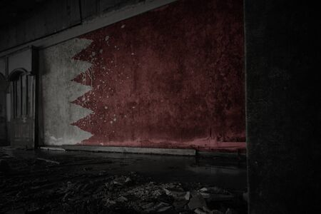 painted flag of bahrain on the dirty old wall in an abandoned ruined house. concept