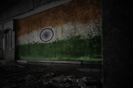 painted flag of india on the dirty old wall in an abandoned ruined house. concept