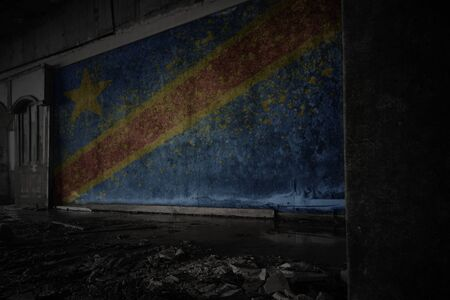 painted flag of democratic republic of the congo on the dirty old wall in an abandoned ruined house. concept
