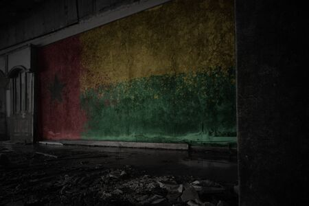 painted flag of guinea bissau on the dirty old wall in an abandoned ruined house. concept Imagens