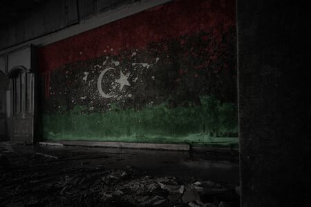 painted flag of libya on the dirty old wall in an abandoned ruined house. concept
