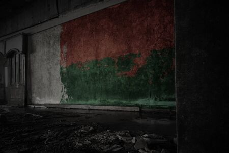 painted flag of madagascar on the dirty old wall in an abandoned ruined house. concept