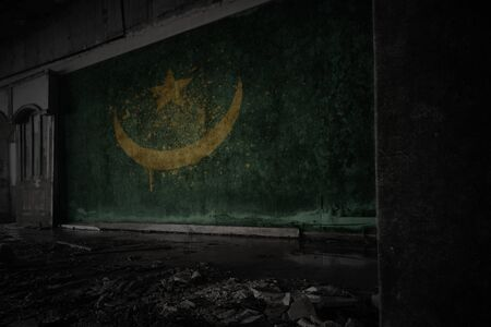 painted flag of mauritania on the dirty old wall in an abandoned ruined house. concept