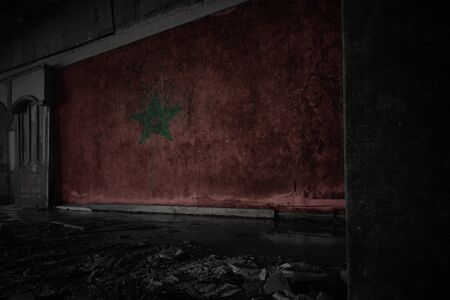 painted flag of morocco on the dirty old wall in an abandoned ruined house. concept
