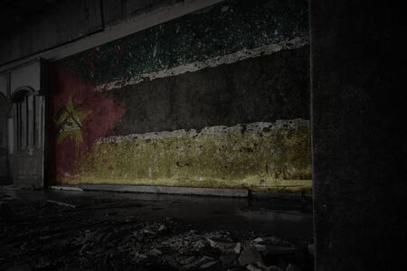 painted flag of mozambique on the dirty old wall in an abandoned ruined house. concept
