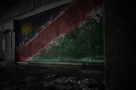 painted flag of namibia on the dirty old wall in an abandoned ruined house. concept