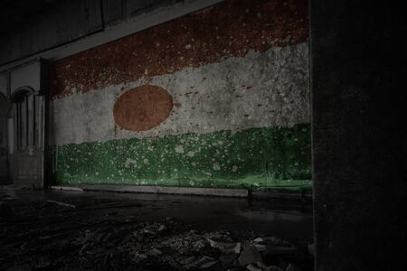 painted flag of niger on the dirty old wall in an abandoned ruined house. concept