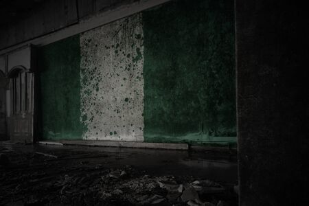painted flag of nigeria on the dirty old wall in an abandoned ruined house. concept