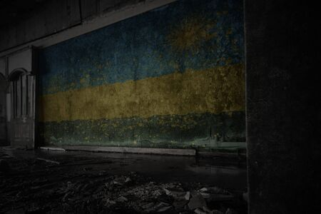 painted flag of rwanda on the dirty old wall in an abandoned ruined house. concept Imagens