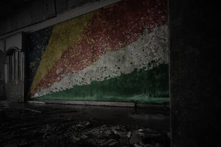 painted flag of seychelles on the dirty old wall in an abandoned ruined house. concept Imagens