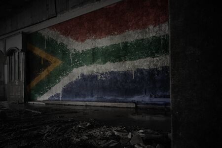 painted flag of south africa on the dirty old wall in an abandoned ruined house. concept