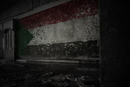 painted flag of sudan on the dirty old wall in an abandoned ruined house. concept
