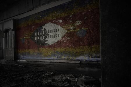 painted flag of swaziland on the dirty old wall in an abandoned ruined house. concept