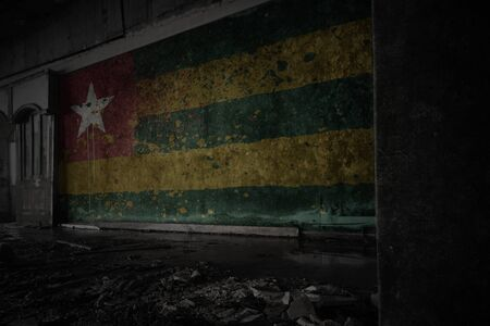 painted flag of togo on the dirty old wall in an abandoned ruined house. concept