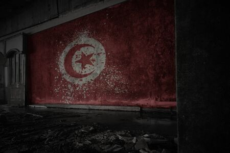 painted flag of tunisia on the dirty old wall in an abandoned ruined house. concept