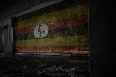painted flag of uganda on the dirty old wall in an abandoned ruined house. concept Imagens