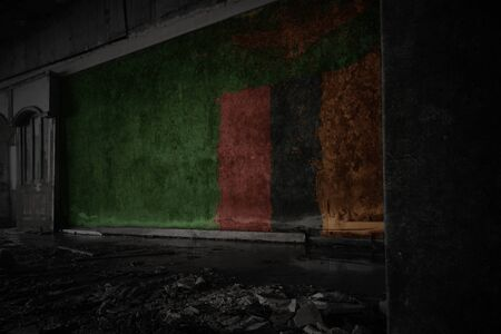 painted flag of zambia on the dirty old wall in an abandoned ruined house. concept Imagens