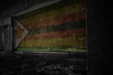 painted flag of zimbabwe on the dirty old wall in an abandoned ruined house. concept
