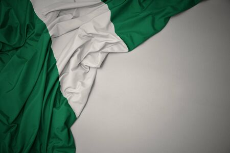 waving colorful national flag of nigeria on a gray background.