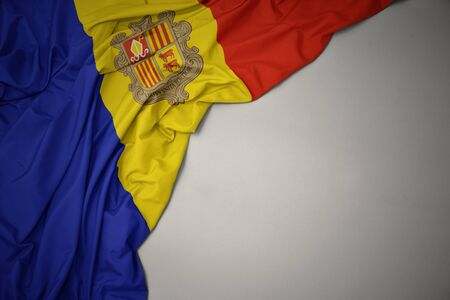 waving colorful national flag of andorra on a gray background. Stock Photo