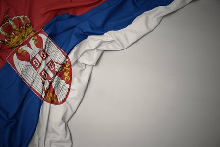waving colorful national flag of serbia on a gray background. Stock Photo