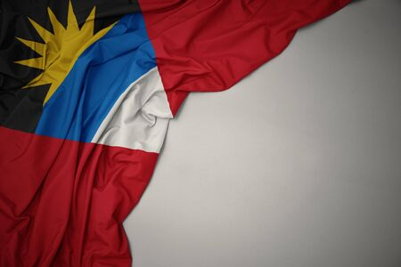 waving colorful national flag of antigua and barbuda on a gray background.