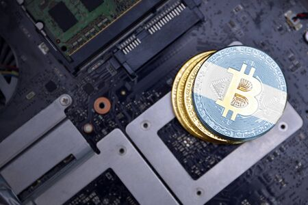 golden shining bitcoins with flag of argentina on a computer electronic circuit board. bitcoin mining concept.