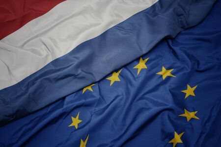 waving colorful flag of european union and national flag of netherlands. macro