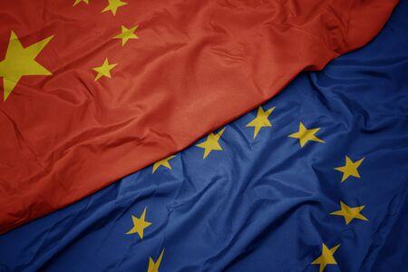 waving colorful flag of european union and flag of china.macro