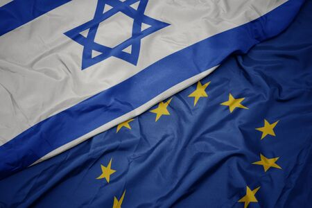 waving colorful flag of european union and flag of israel.macro