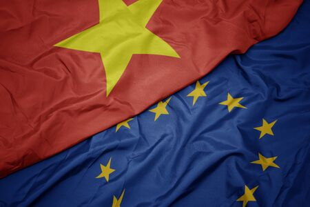 waving colorful flag of european union and flag of vietnam.macro 免版税图像